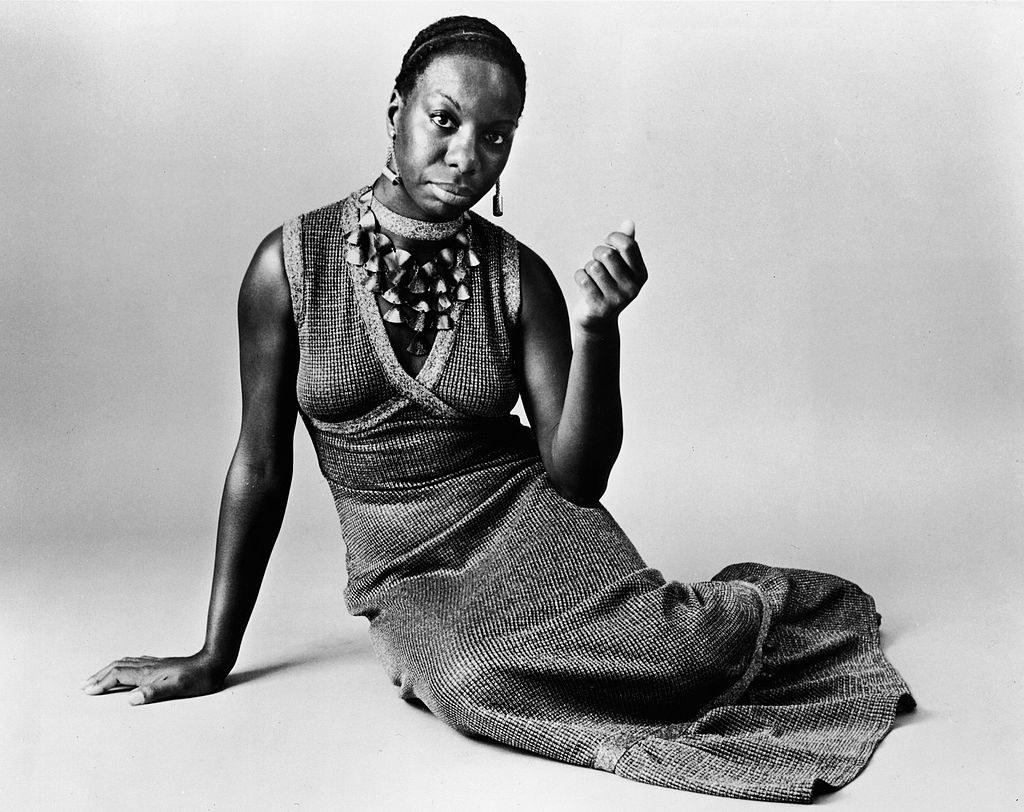 Black and white photograph of Nina Simone posing on a floor