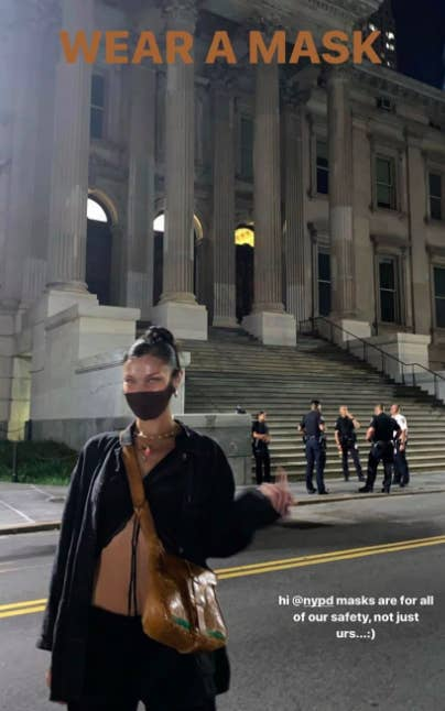 Bella Hadid wearing a mask posing for a photo while flipping off the camera with unmasked officers behind her