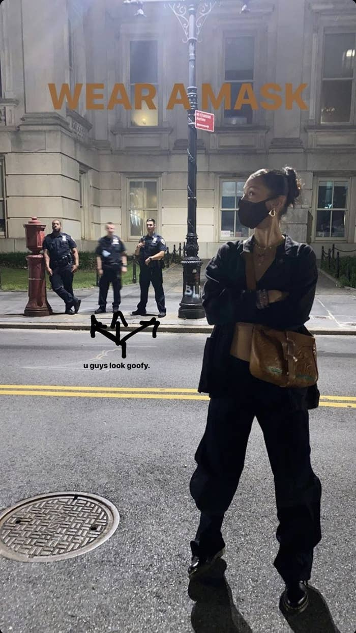 Bella Hadid standing on a street at night with her arms crossed wearing a mask, with three unmasked officers behind her in the distance
