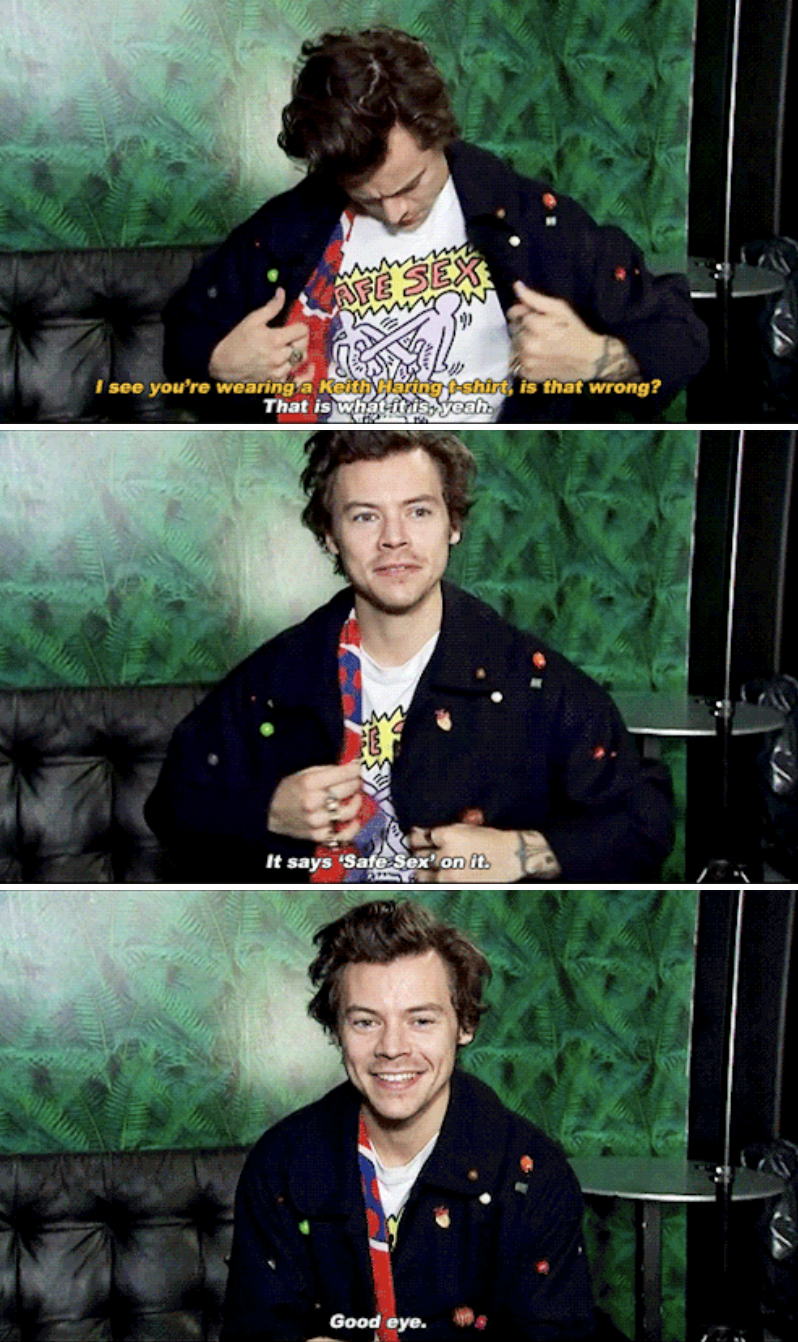 """Harry showing off his shirt and answering the interviewer: """"It says 'Safe Sex' on it. Good eye"""""""