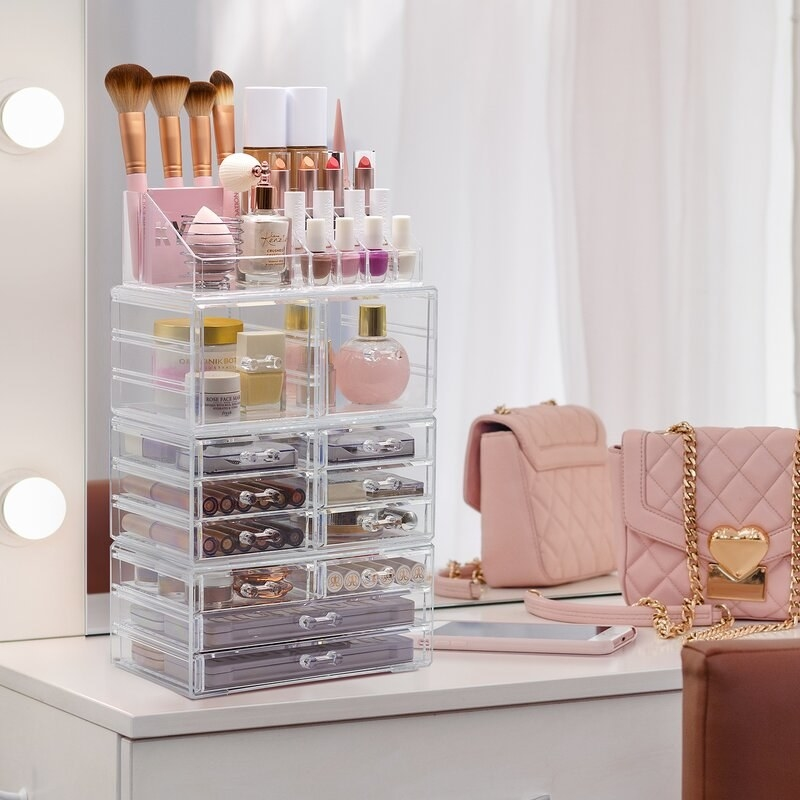 An acrylic cosmetic holder with 12 drawers and an upright unit attached to the top