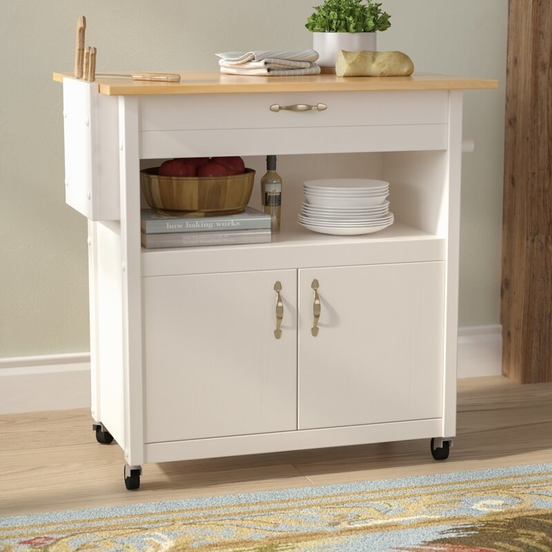 A white kitchen cart on casters with a large cabinet, an open shelf, a skinny drawer, a wood countertop, and an attached towel rack