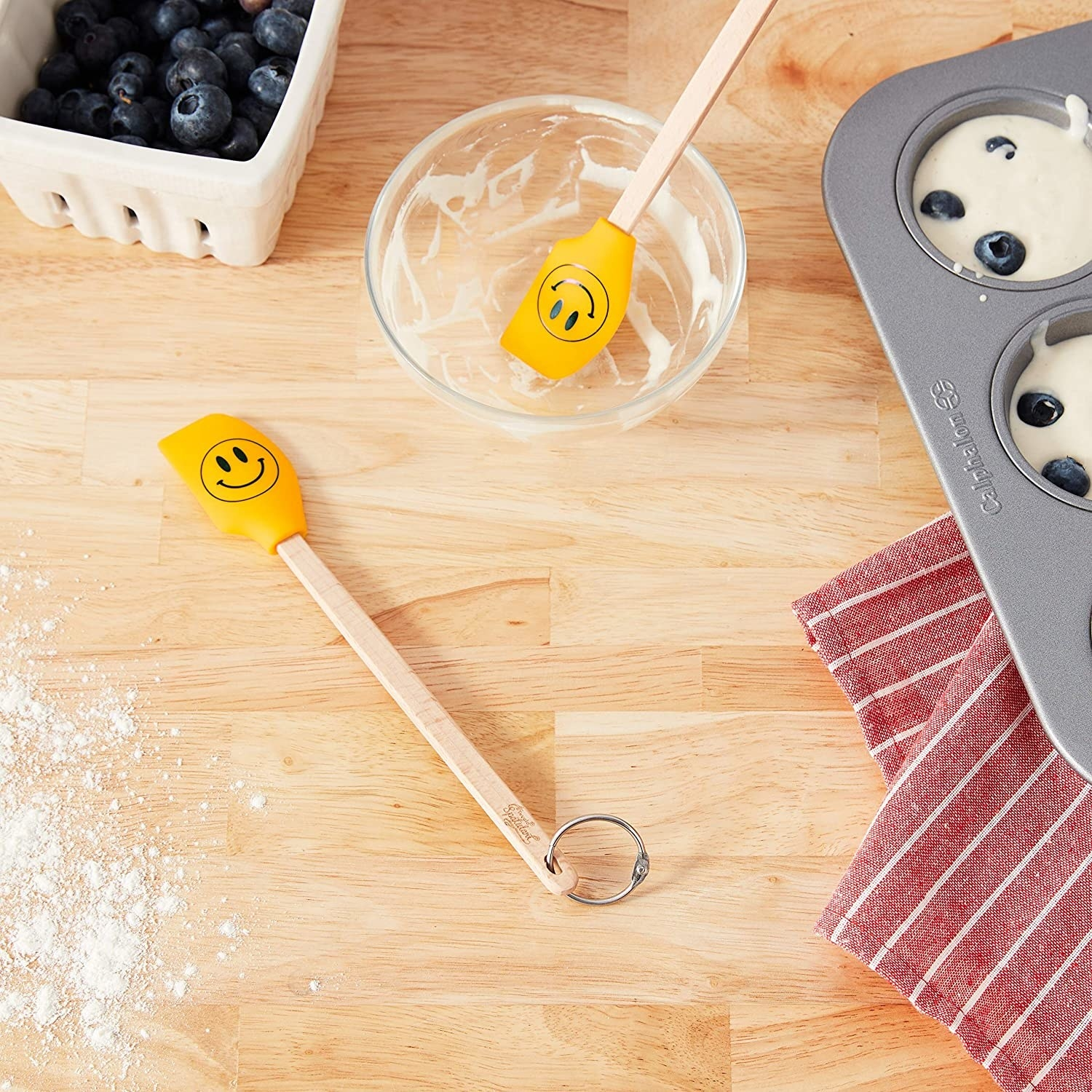 Two smiley face spatulas surrounded by baking supplies