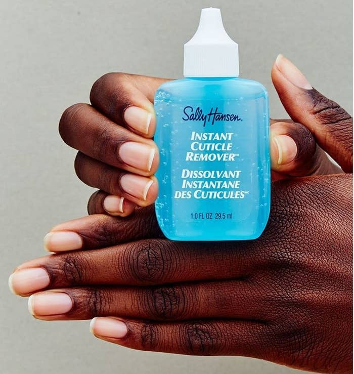 A person holding a bottle of instant cuticle remover