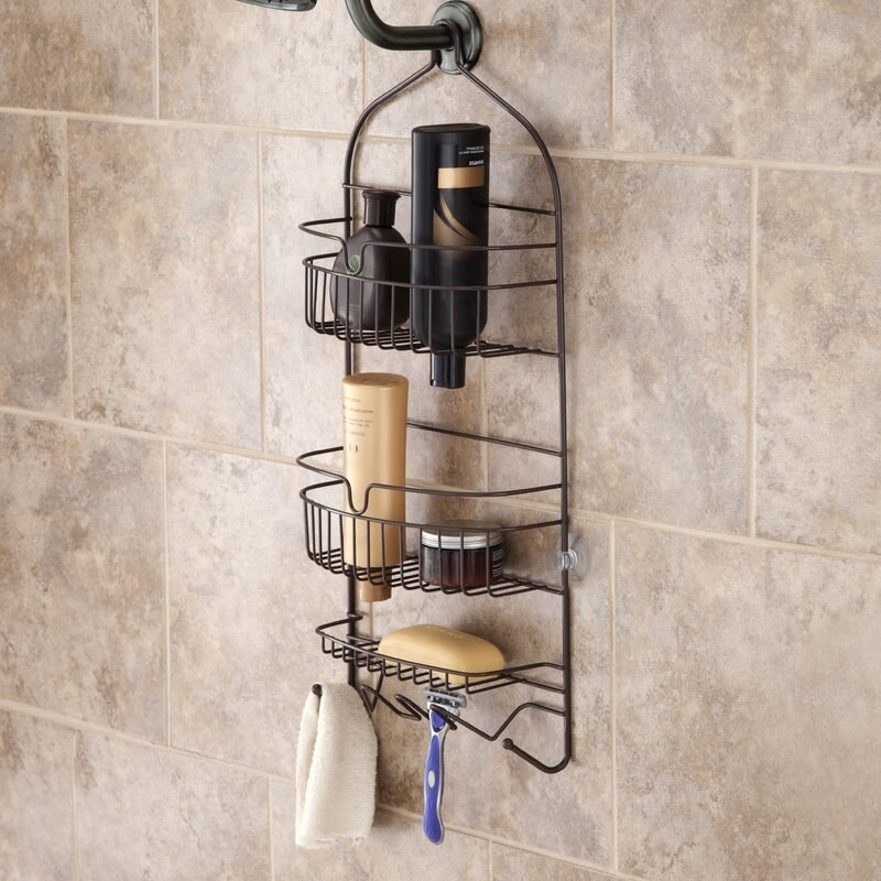 A black, wire shower caddy hanging from a shower head