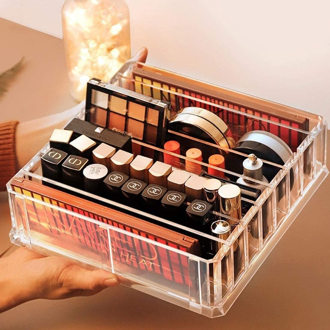 A person holding the makeup organizer filled with makeup