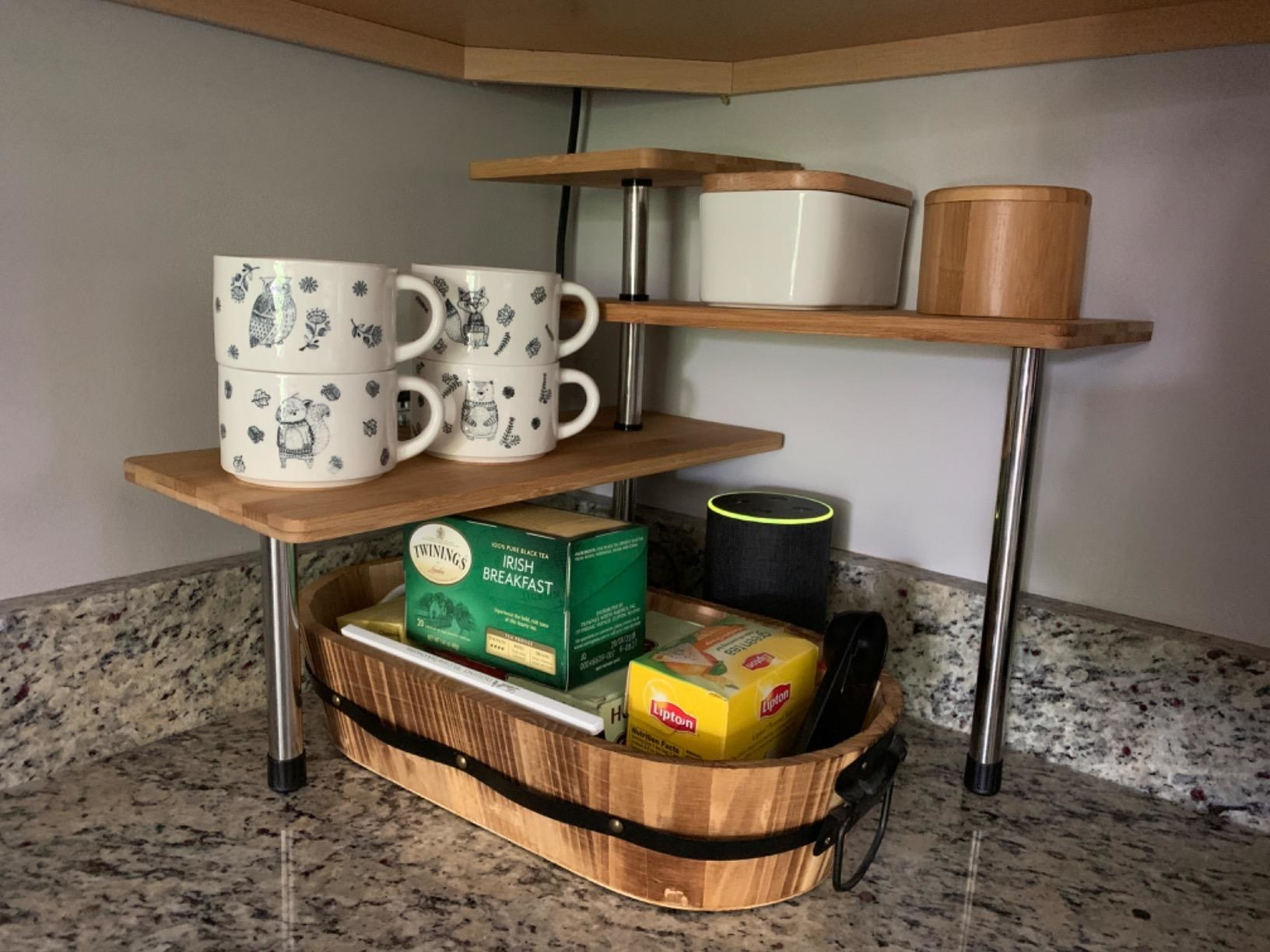 Reviewer pic of the three-tier shelves with wood tops and silver legs in the corner of a counter with mugs and assorted other products on it and below it