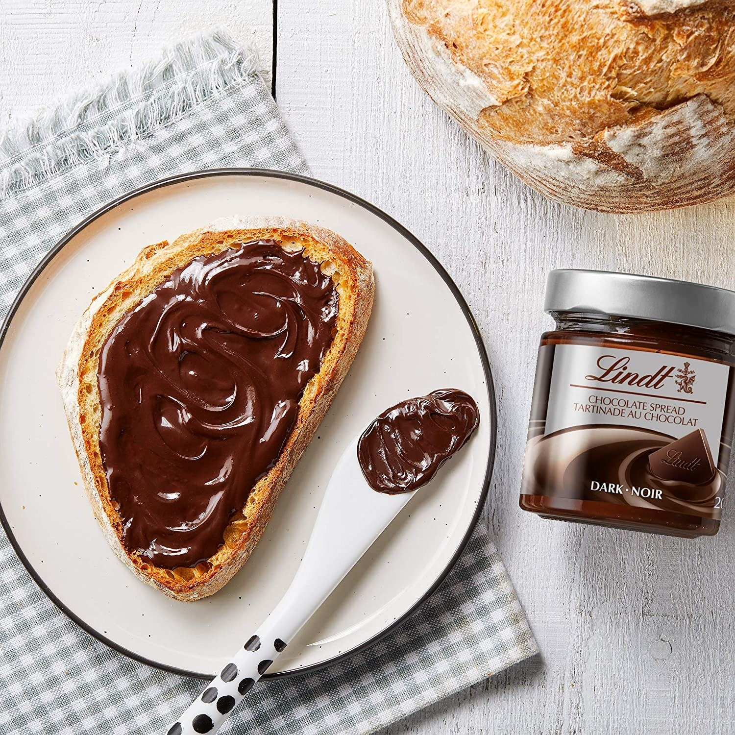 A piece of toast covered in Lindt chocolate spread next to the jar