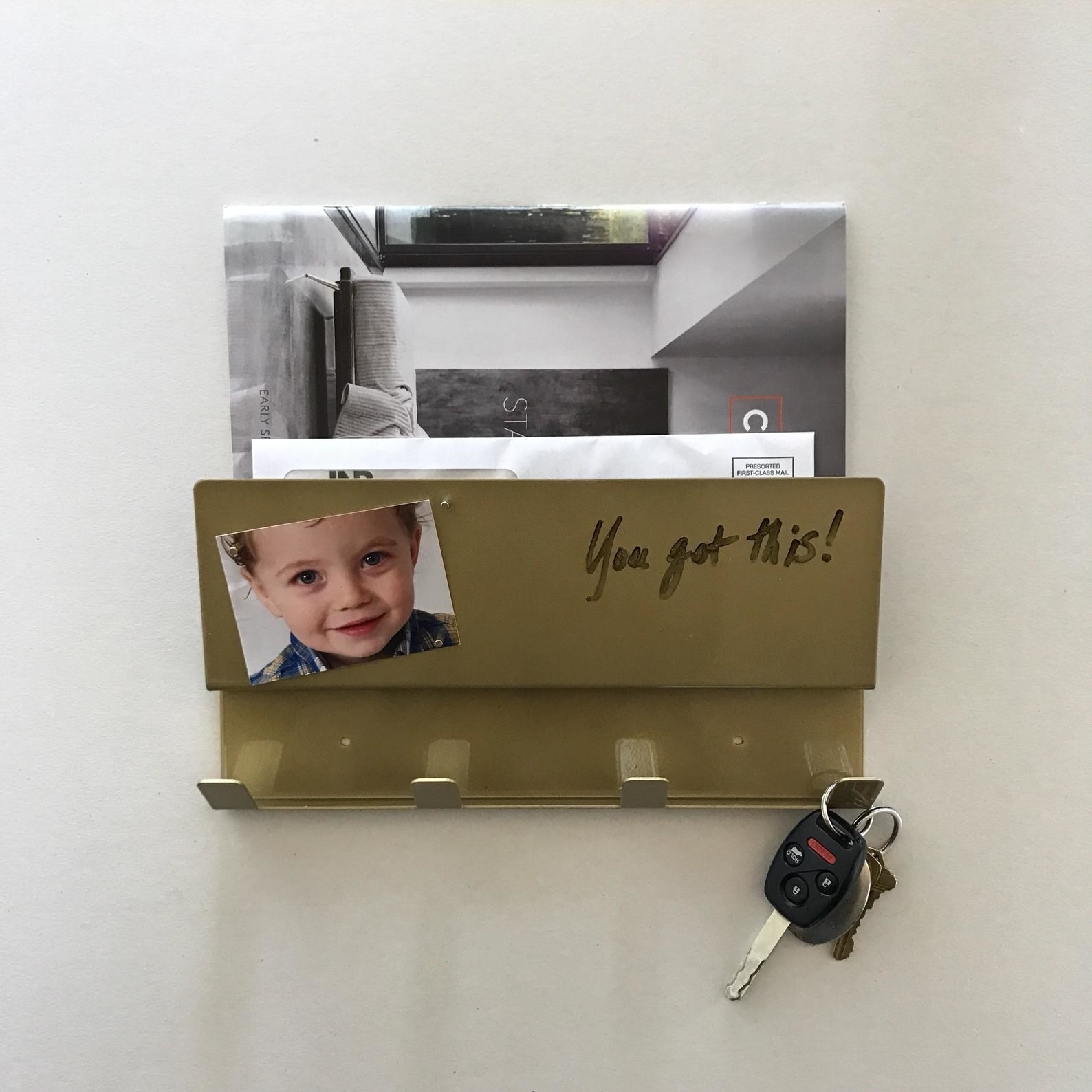 "Gold organizer with a slot with mail in it and four hooks with a key on one plus a picture on the front with the words ""You got this!"" written next to it"