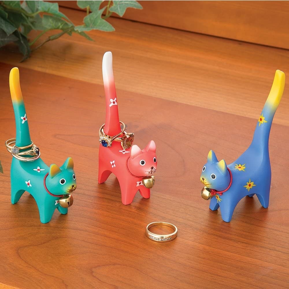 Three cat-shaped ring holders with rings on them