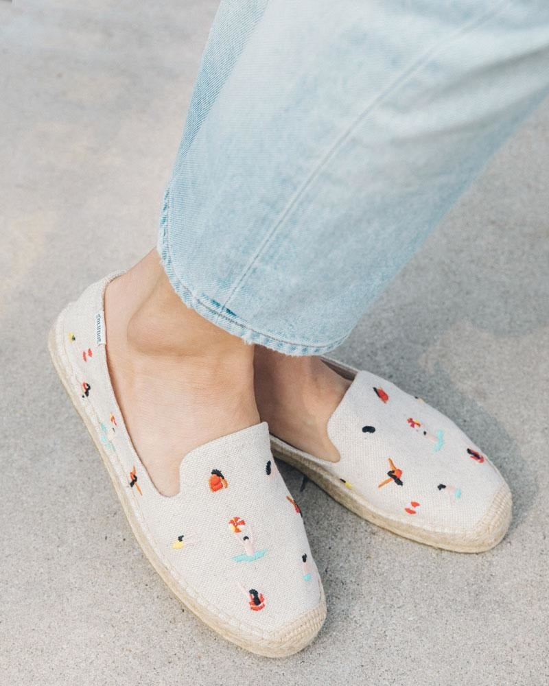model wearing beige espadrilles with illustrations of swimmers
