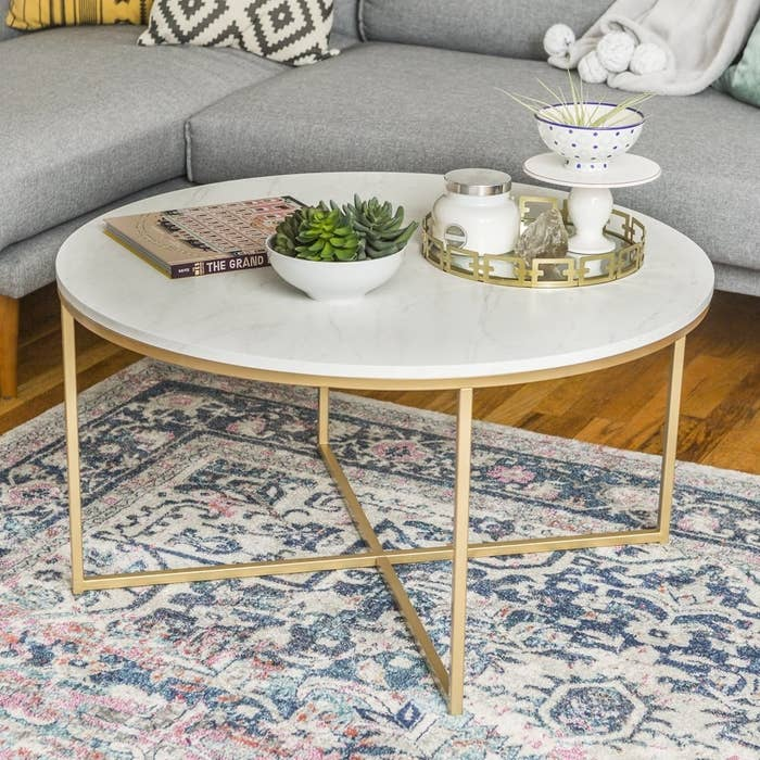 a round faux white marble coffee table with gold legs