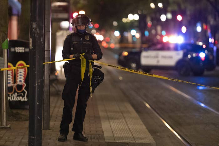 """A police officer wearing a helmet ties tape reading """"POLICE TAPE DO NOT CROSS"""" around the crime scene while a squad car flashes its sirens in distant background"""