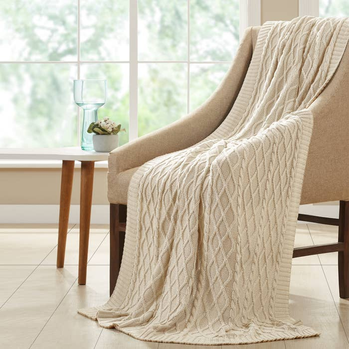 A beige cable knit blanket draped over a chair