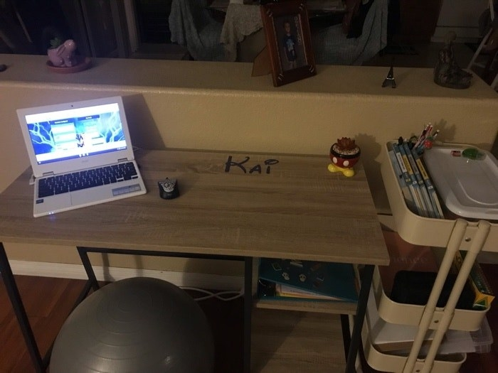 A mom's at-home school desk for her son, with a sensory chair and laptop.