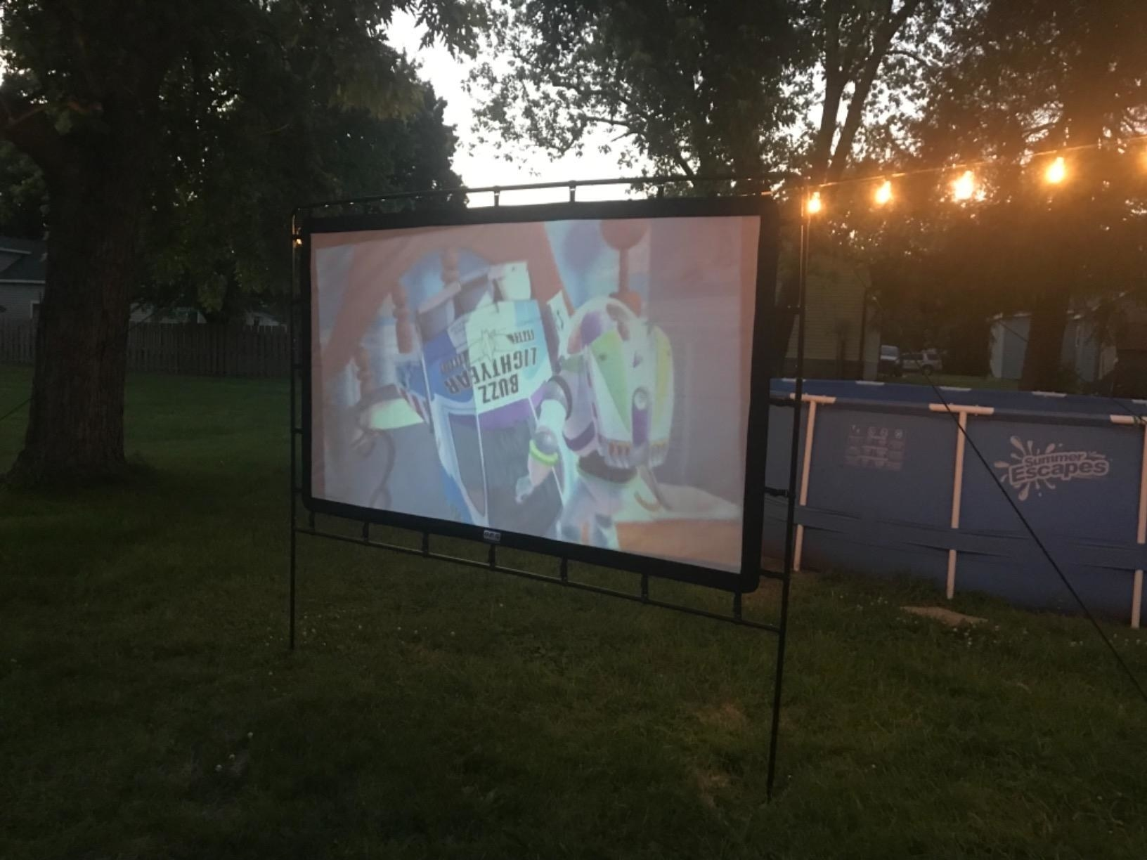 Reviewer photo of the movie screen set up in a backyard with Toy Story playing on the screen