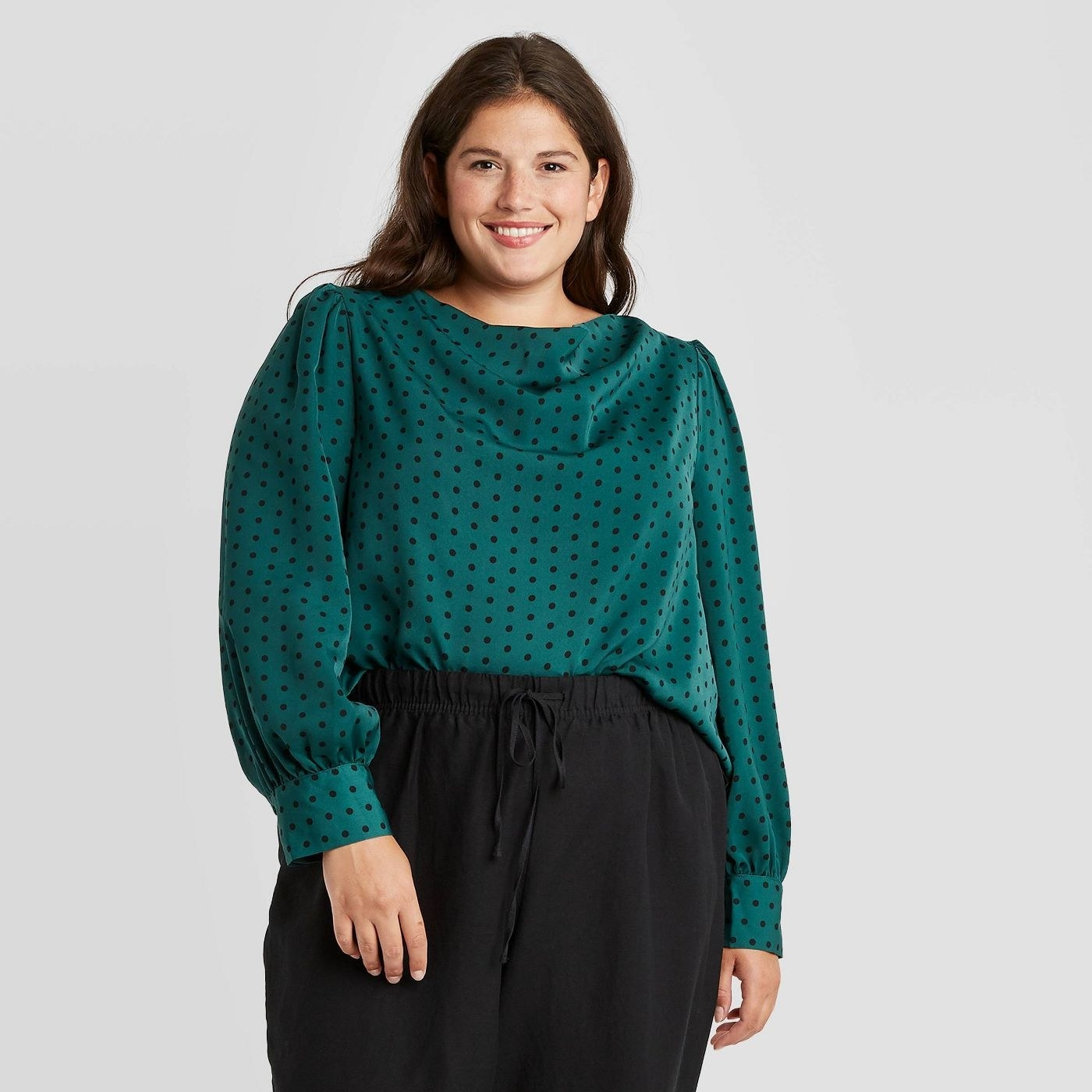 Model wearing the silk green top with small black polka dots