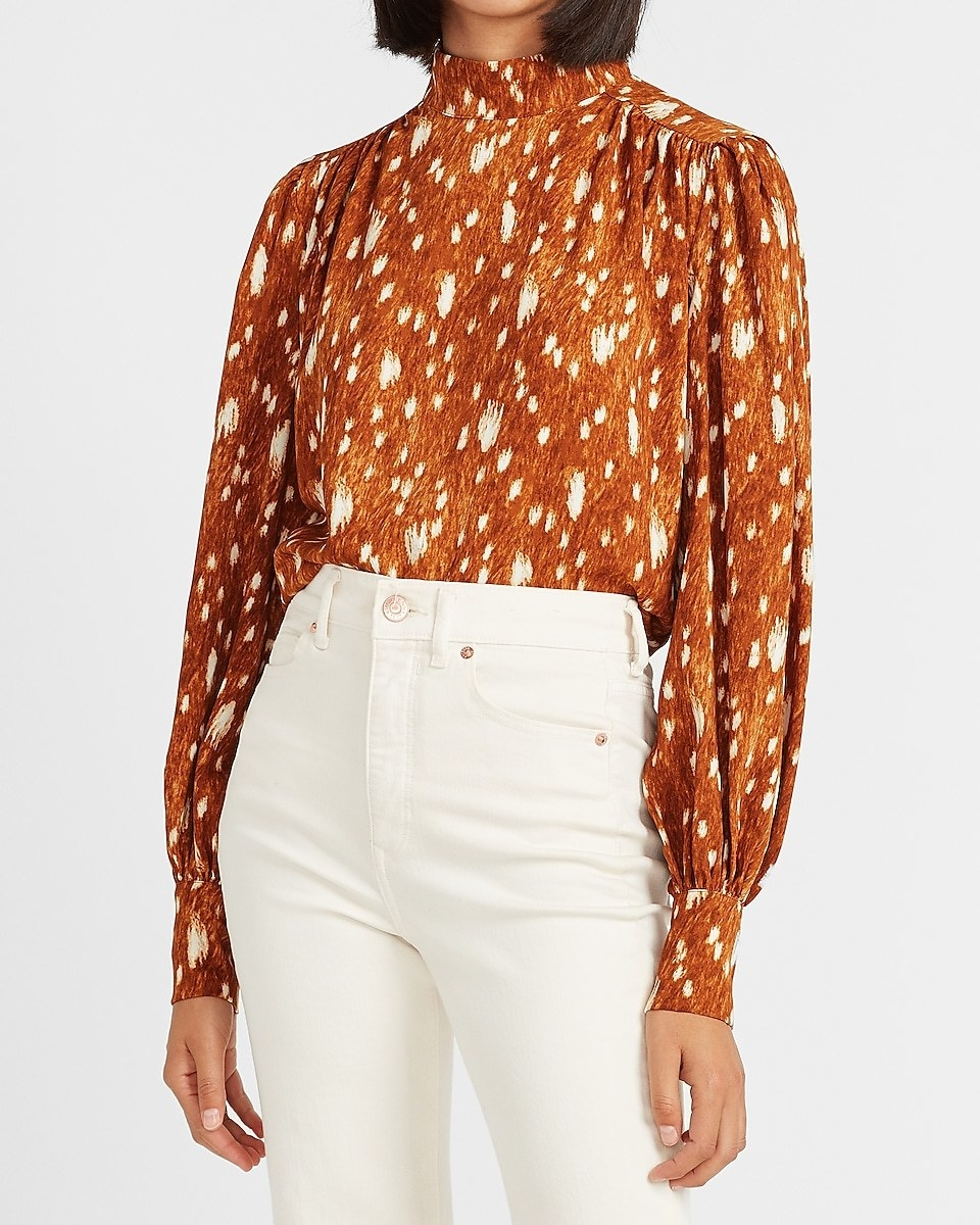 A model wearing the voluminous long sleeve mock neck top with a fawn-like brown and white pattern
