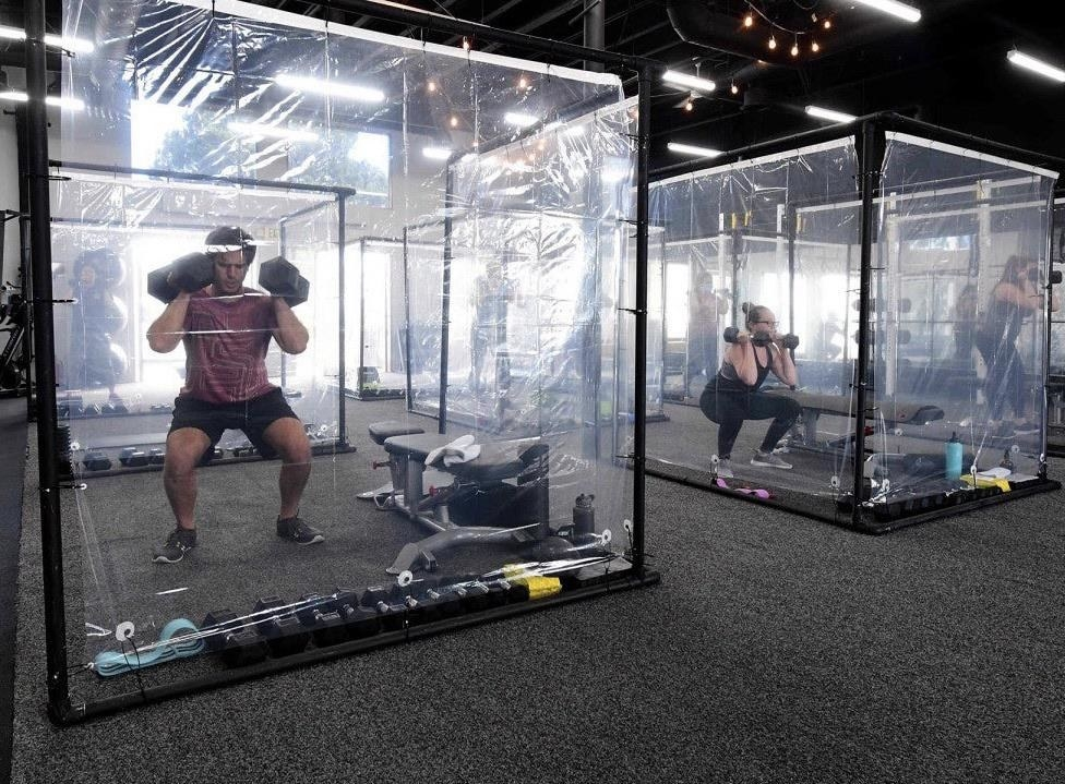 People working out in plastic cubicles at a gym