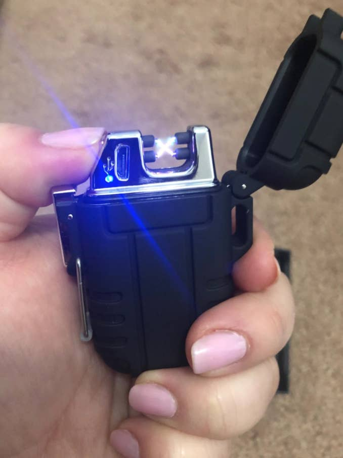 A reviewer holding the small, black lit plasma lighter