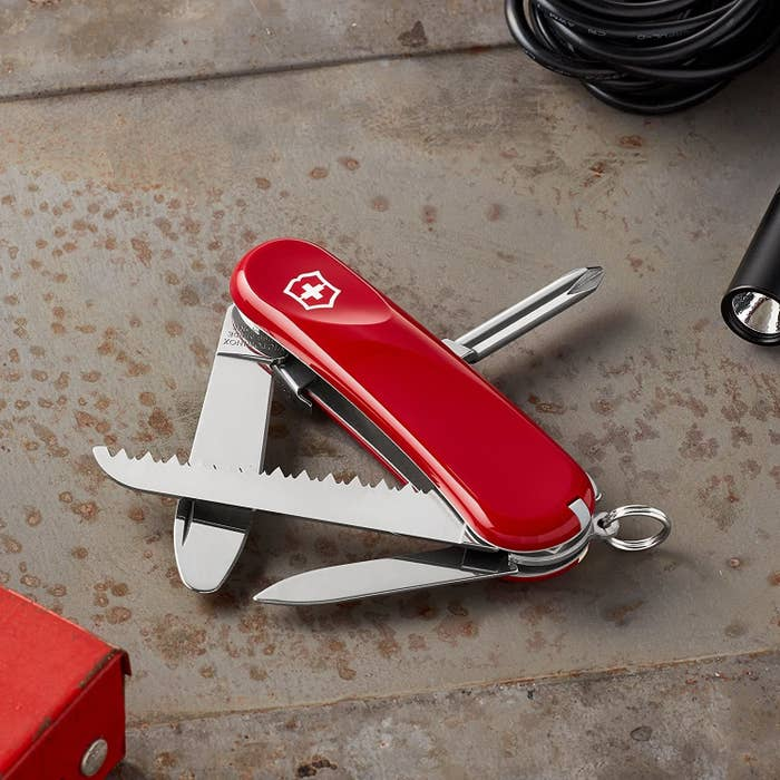 A red Swiss Army knife with a saw, screwdriver, and other tools partially opened