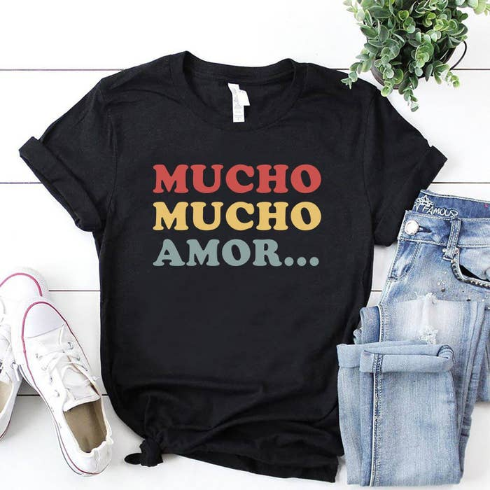 """A black t-shirt with the words """"Mucho mucho amor"""" in red, yellow, and green"""