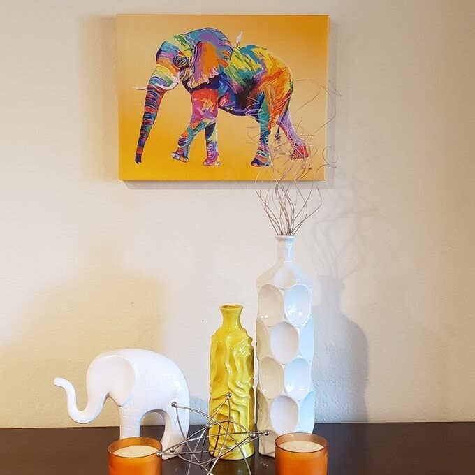 a canvas painting with a yellow background and elephant painted in all the colors of the rainbow