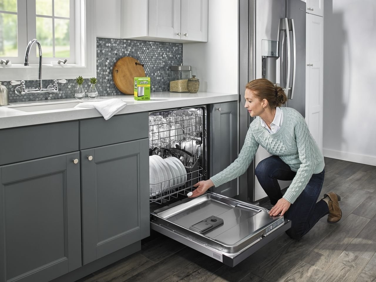 A woman places an Affresh dishwasher cleaning tab into a full dishwasher