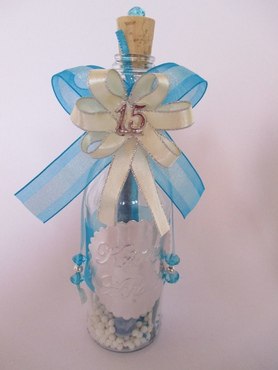 A small bottle with white beads inside and blue ribbon tied around it and with 15 written on it