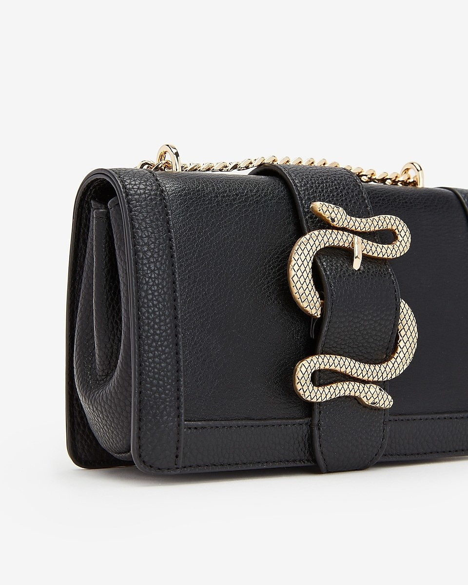 A small black bag with a buckle detail shaped like a double-ended snake with a gold chain strap