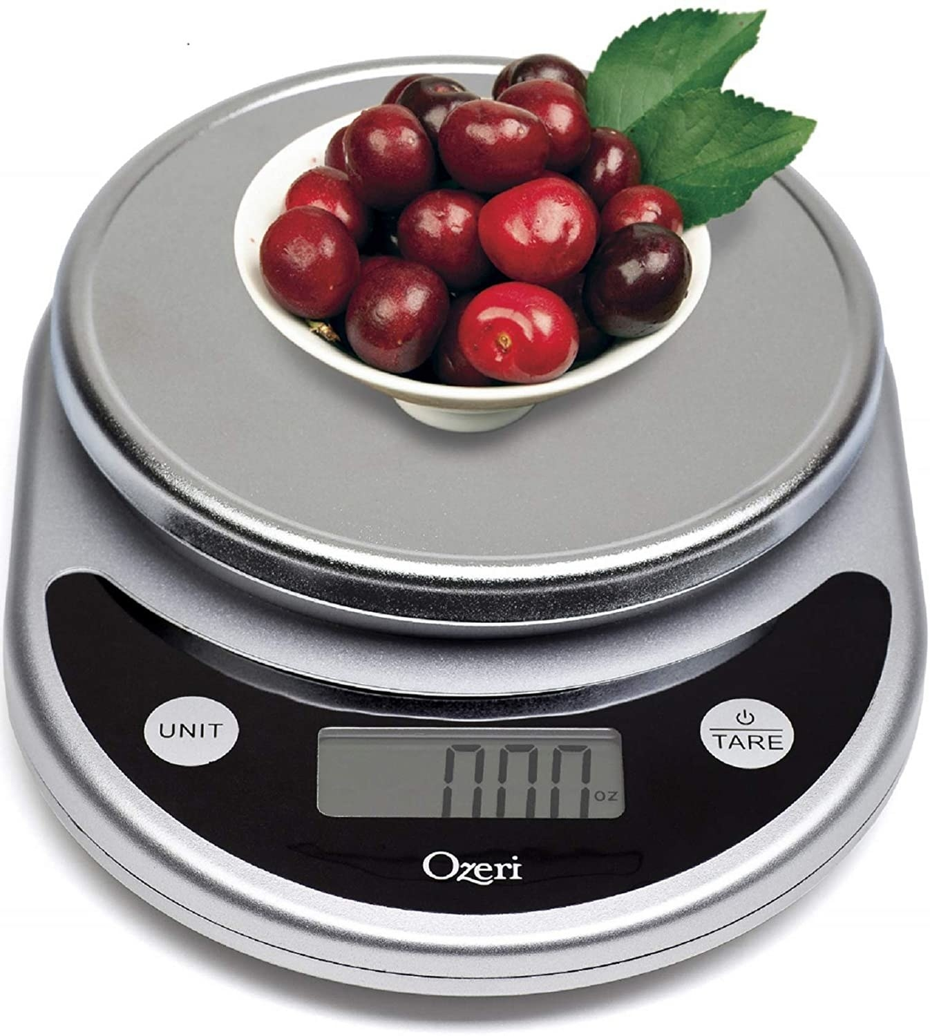 A digital food scale with cherries on top