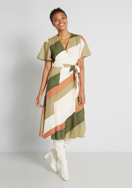 a model in a wrap dress with a design of white, green, light green, and orange vertical color boxes