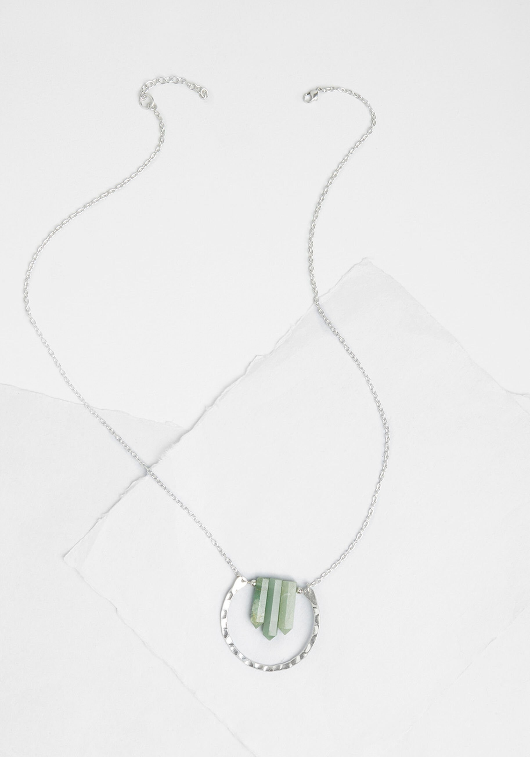 the silver necklace with a horseshoe-shaped hoop and three small jade colored crystals in the middle