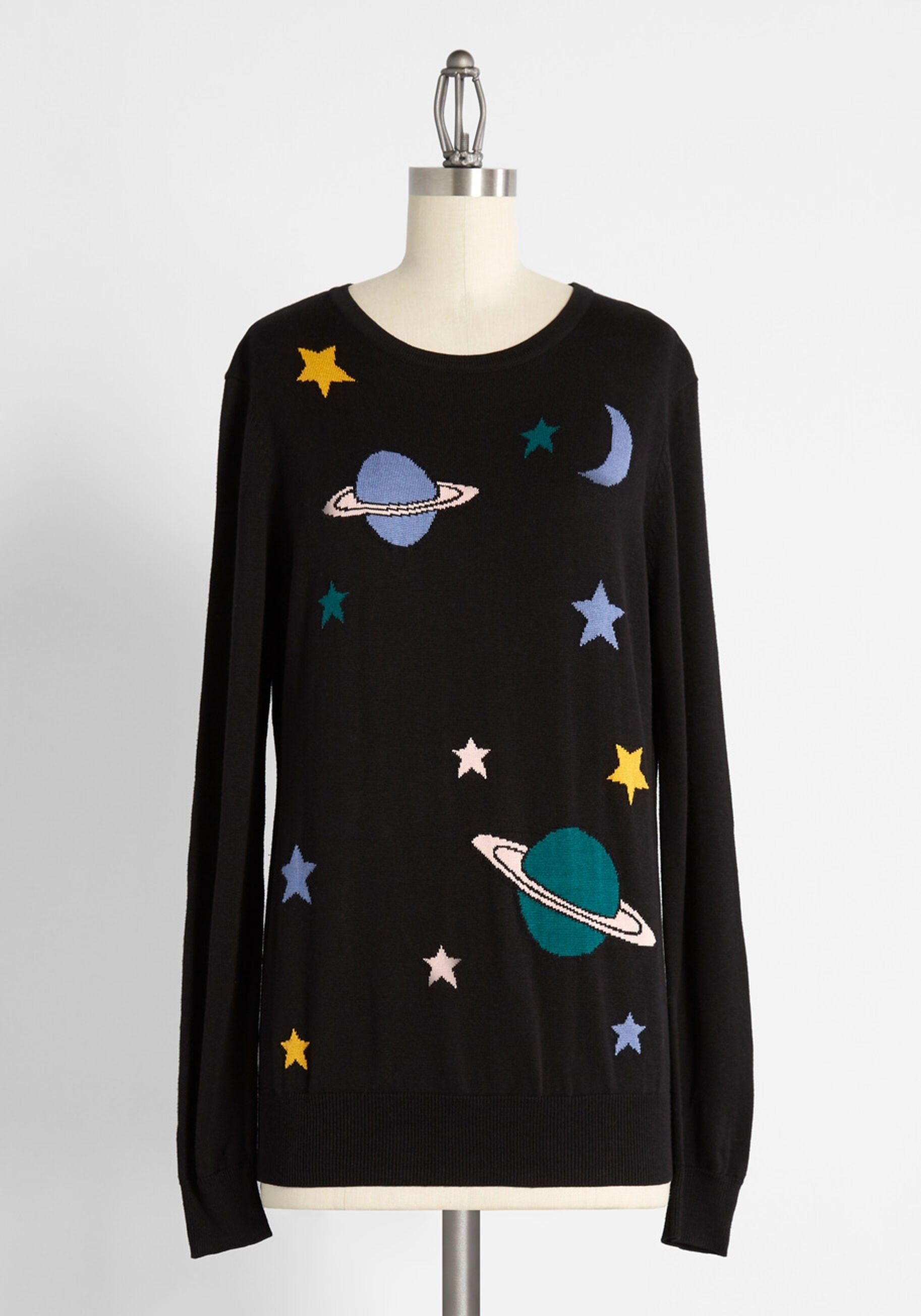 a black sweater with stars and saturn on it