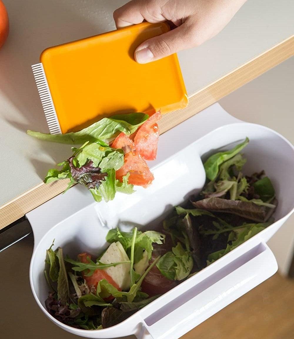 A person scraping salad into the scrap bin