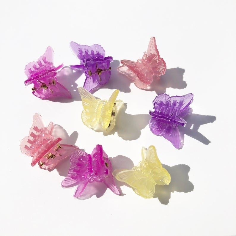 Eight butterfly clips on: two pink, two yellow, two purple, and two hot pink