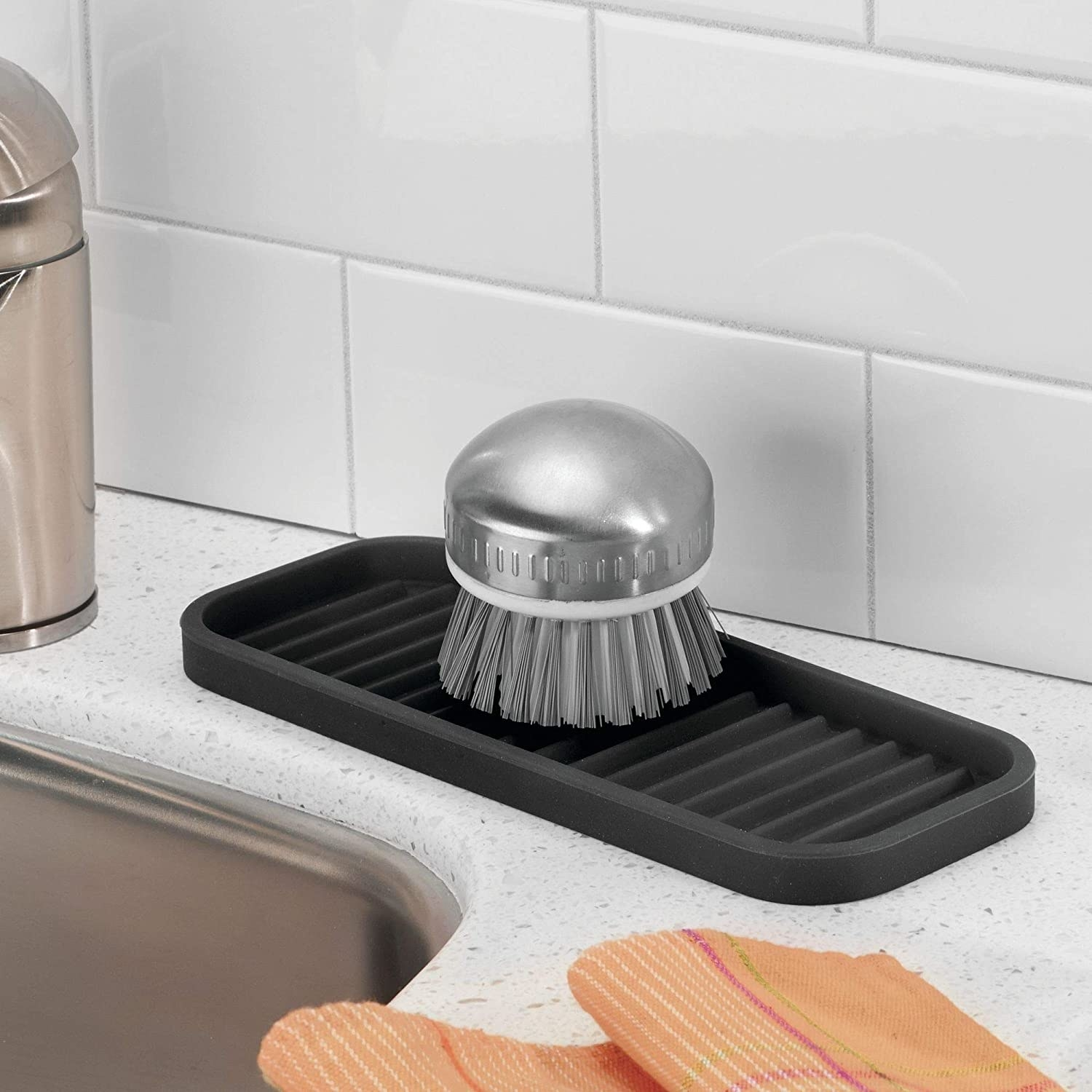 A scrub brush on top of the silicone kitchen sink tray