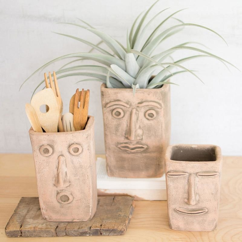 A set of three vases in small, medium, and large in a red clay color with faces on the front of them and utensils and a plant in two of them