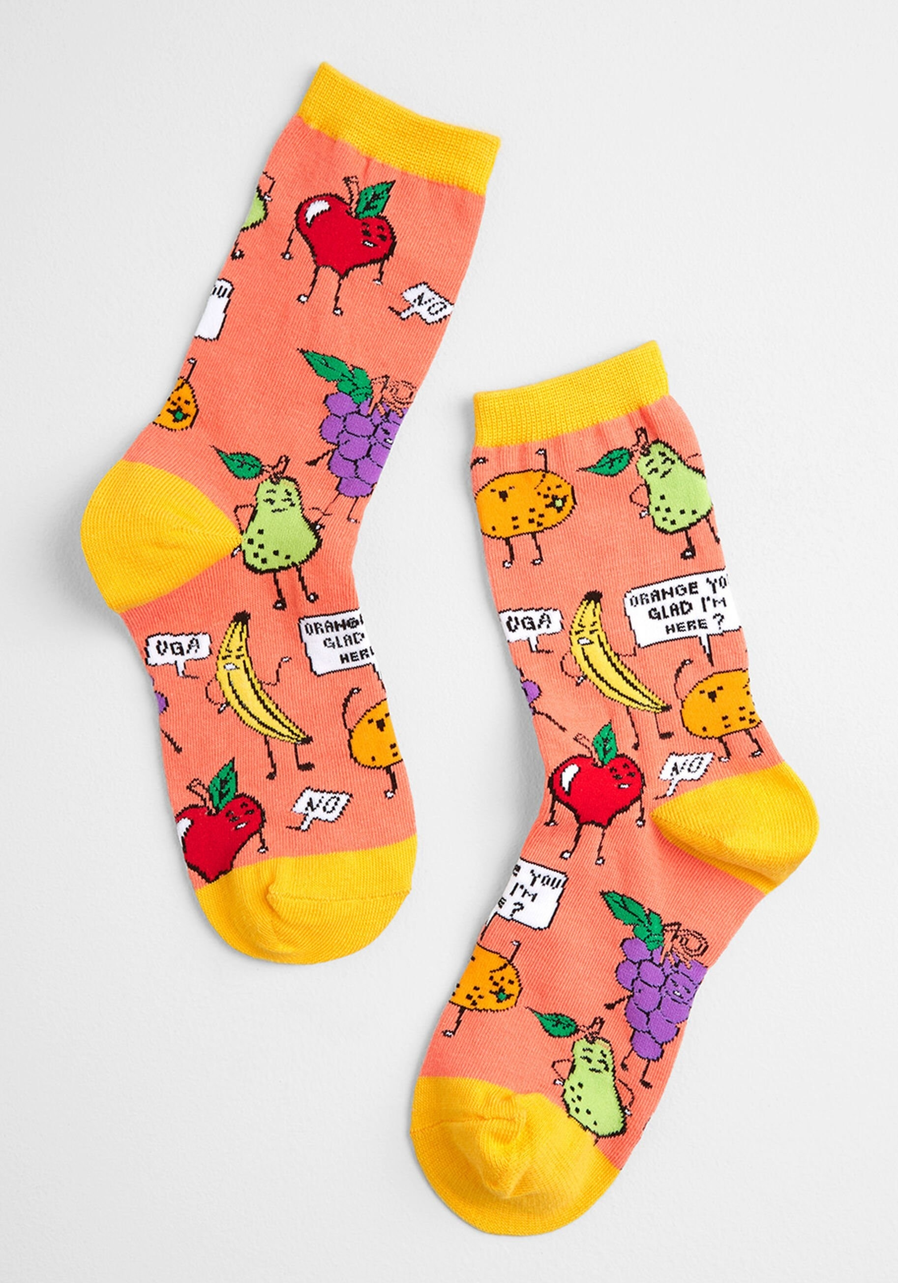"a pair of orange socks with yellow tips and heels, covered in fruits and signs that say ""orange you glad I'm here"""