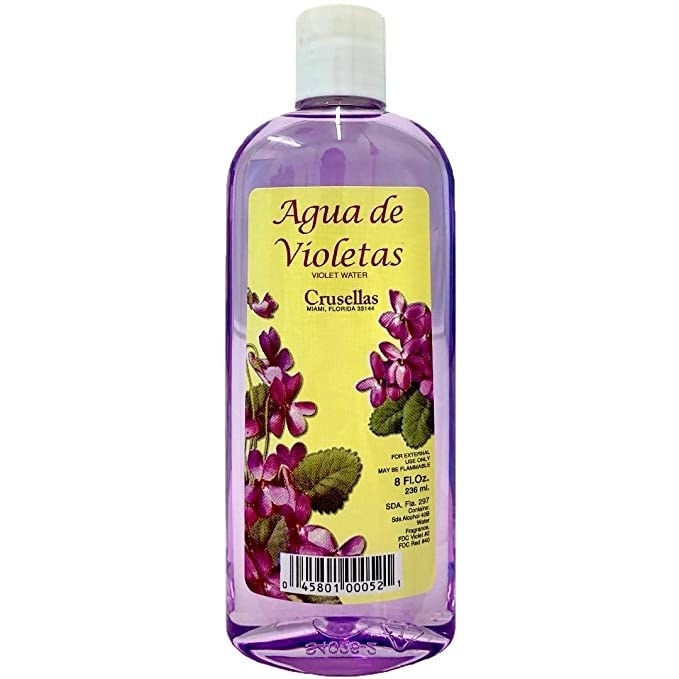 A bottle of Agua de Violetas which is clear with purple perfume inside of it and violets on the label