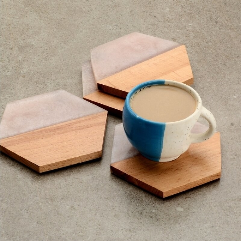 four coasters on a surface with a mug of coffee sitting on one. They are half-wood and half-quartz