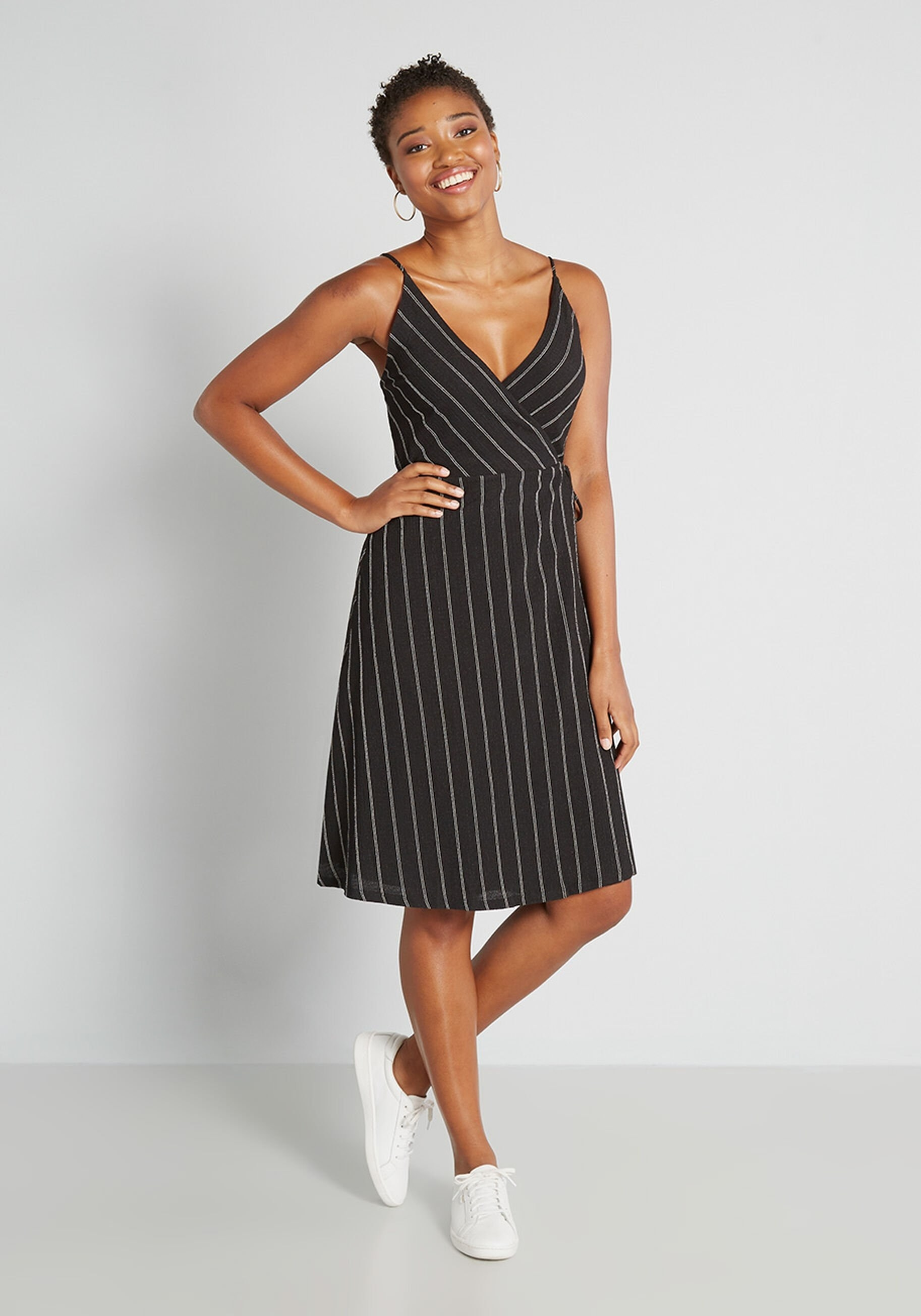 a model in the mid-length black dress with white thin vertical stripes