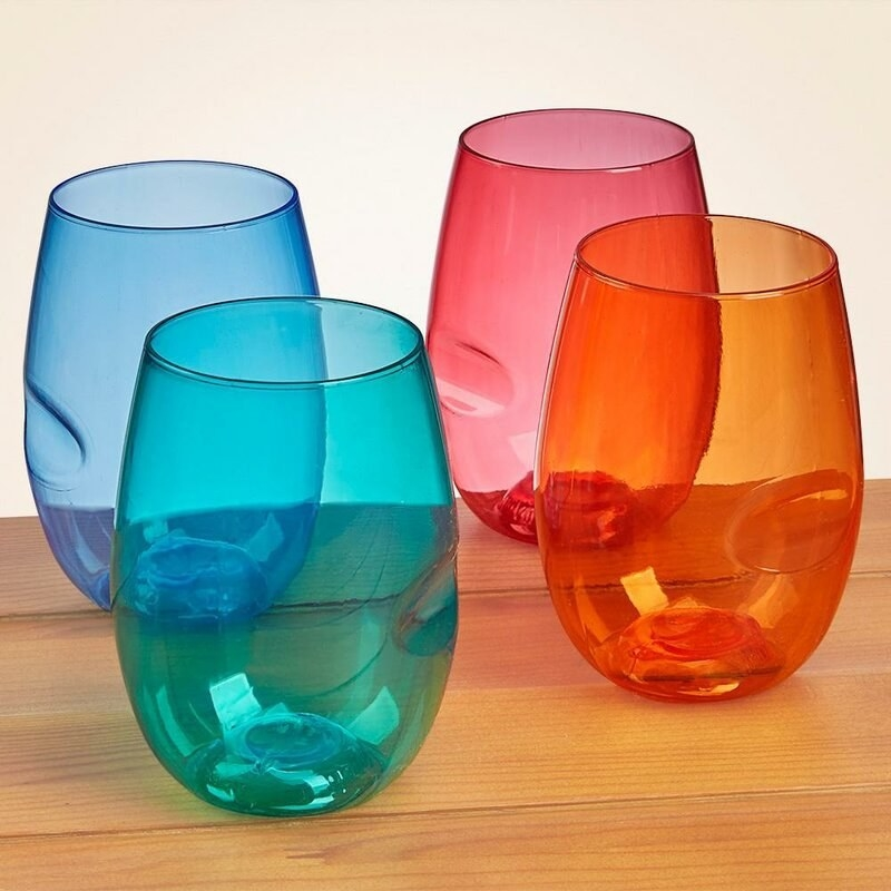 four stemless wine glasses. They are red, orange, teal, and blue respectively.
