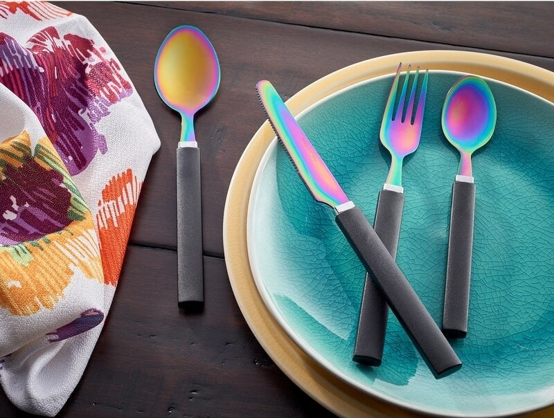 a knife, fork, teaspoon, and regular spoon on a plate. They have black handles and the dipping portion of the them have a rainbow look