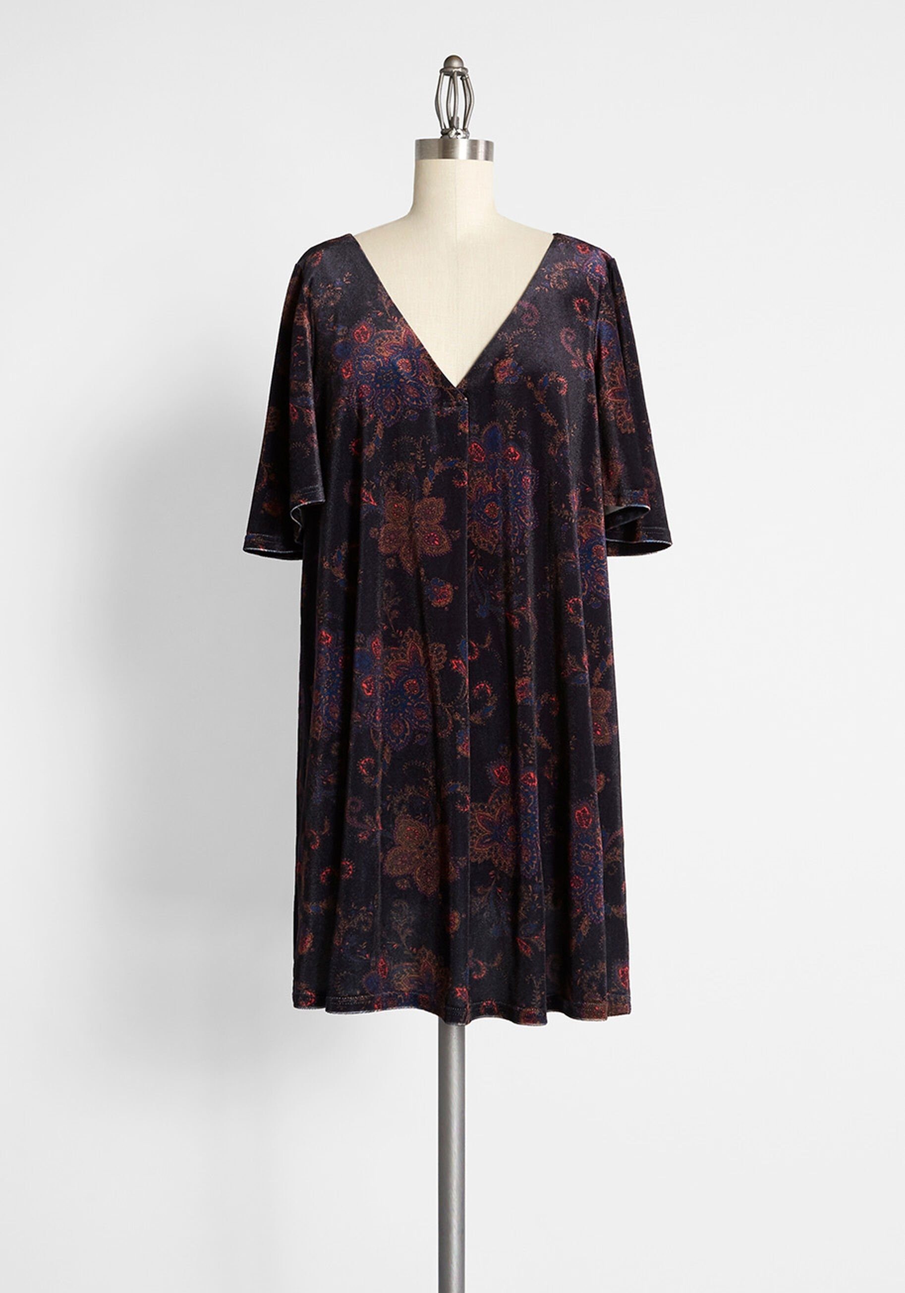 a black dress with an orange, pink, and blue-hued paisley-adorned frock has short, flounce sleeves