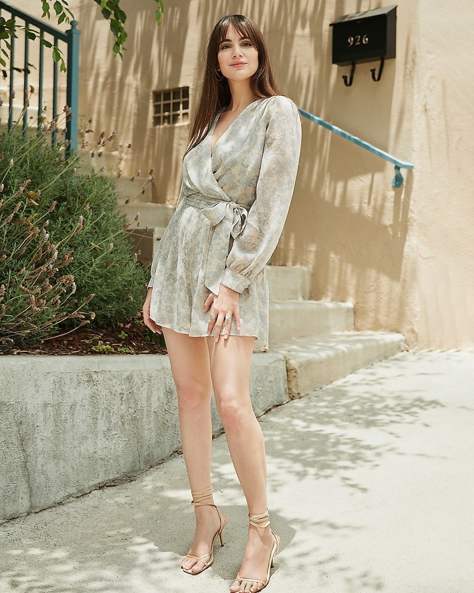 A model wearing the cream, tie-waist romper with a pale blue floral print