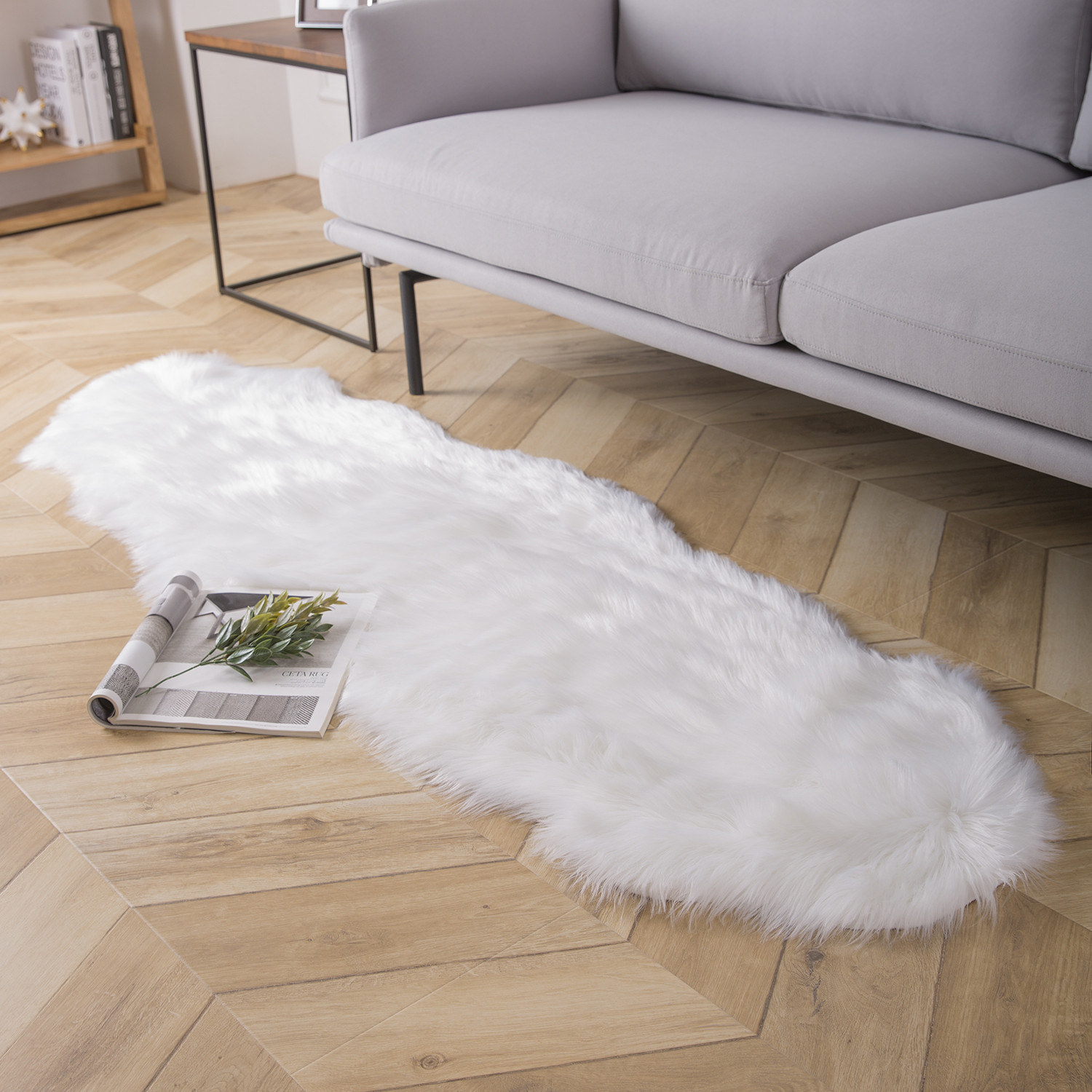 A white faux fur rug on the floor next to a couch