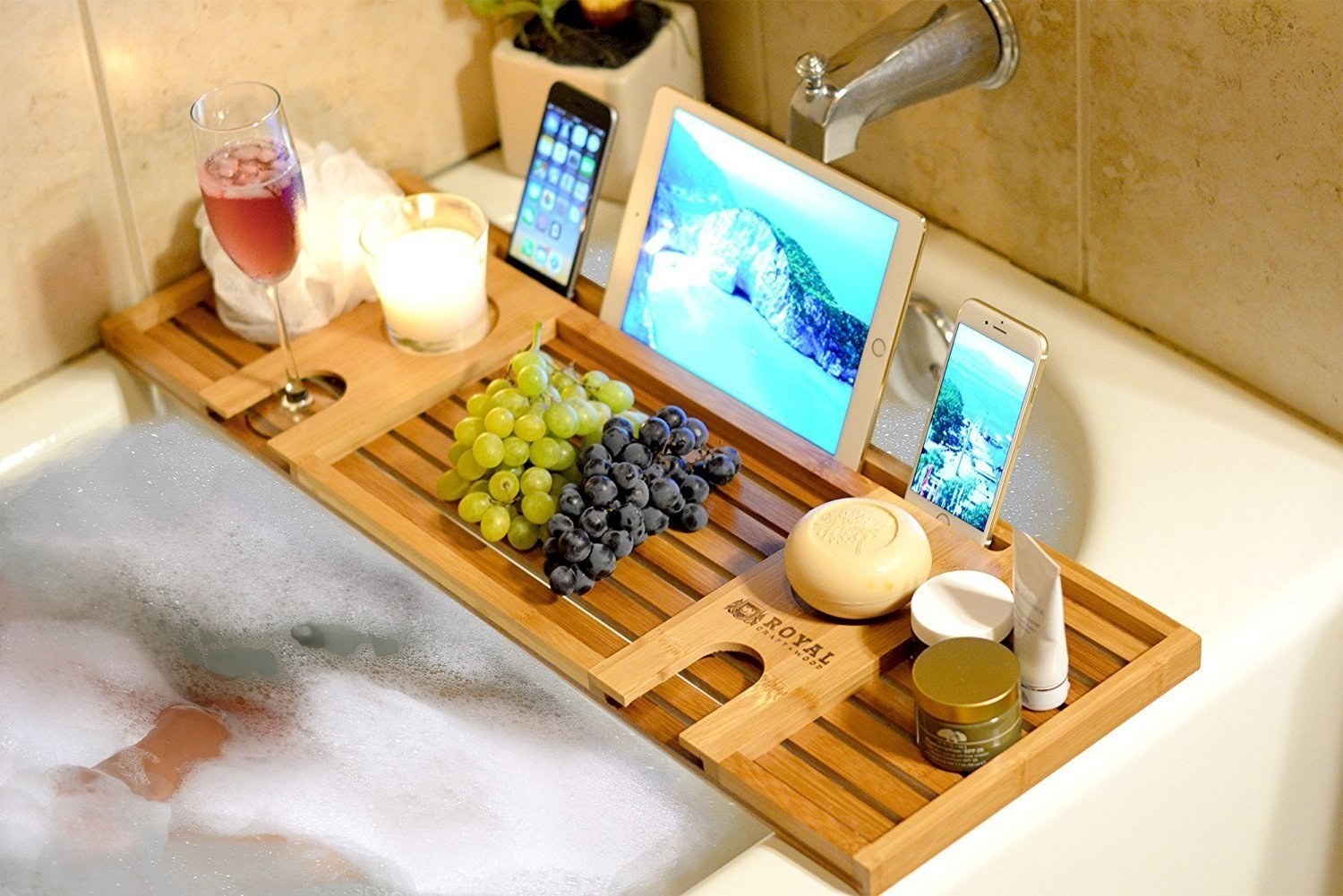 A bamboo bath tray holding grapes, a tablet, two phones, and various beauty products.