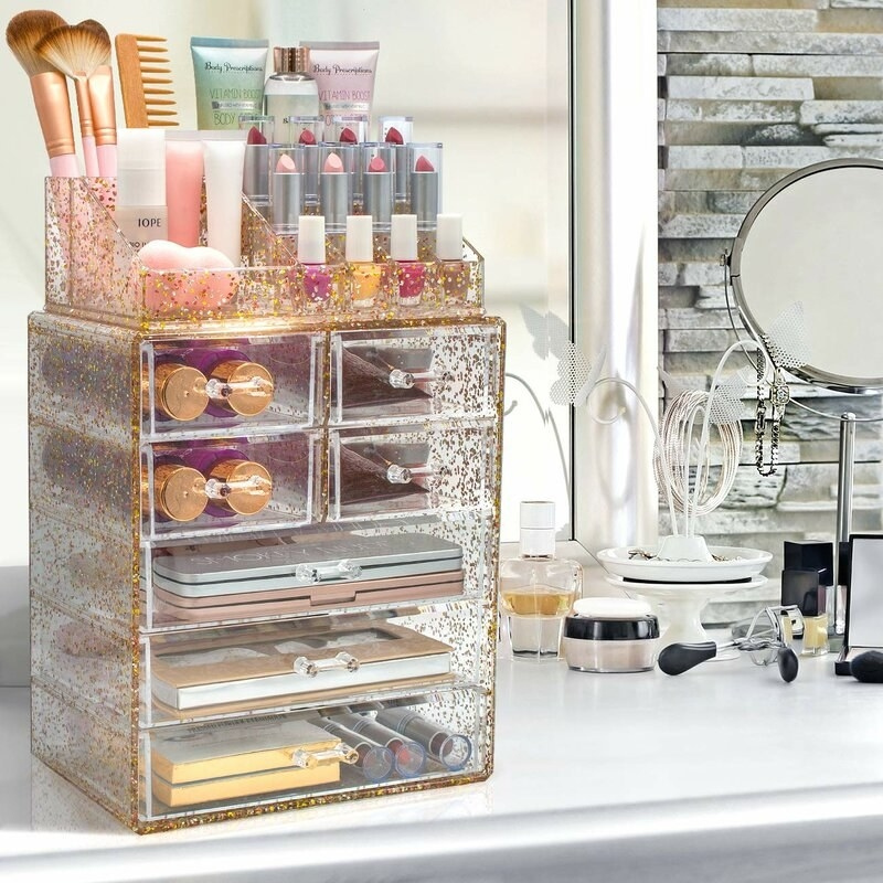 the organizer is made of clear acrylic and has golden glitter specks all over it