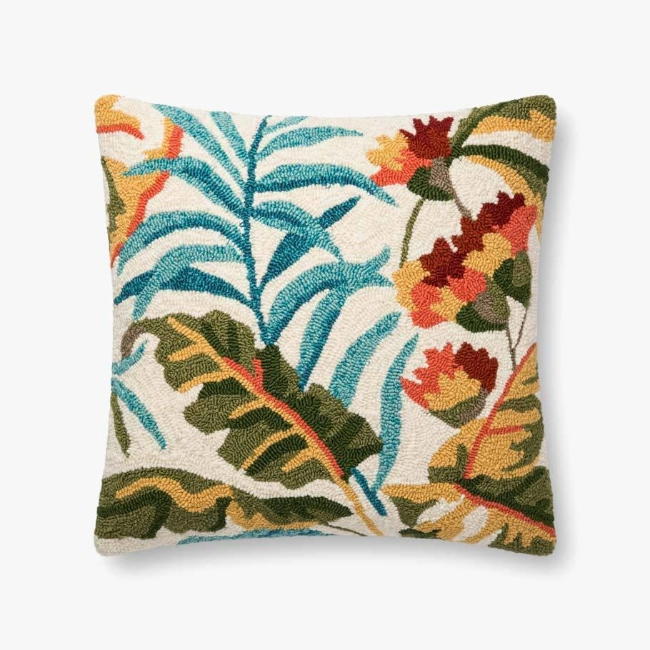 The cream pillow, which has green palm fronds and flowers on it